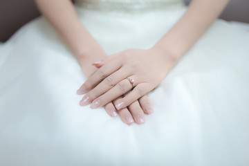 Hands of the bride tenderly and gently lay on her lap