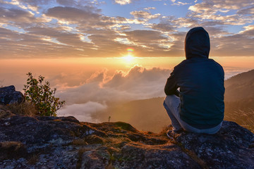Man sitting on a mountain for watching Sunrise views alone.