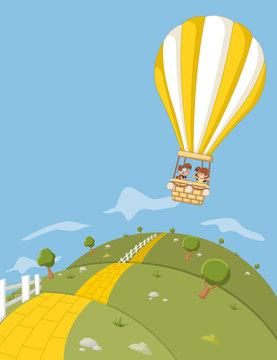 Cartoon kids inside a hot air balloon flying over green hills with a yellow brick road.