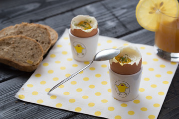 Soft boiled eggs with bread on white napkin with yellow dots.