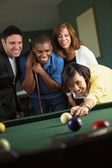 Group of young friends playing billiard.
