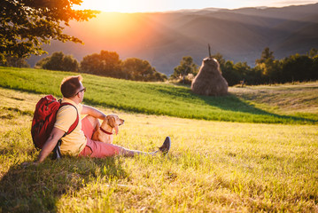 Man and dog sitting on a mountain meadow and enjoying sunset