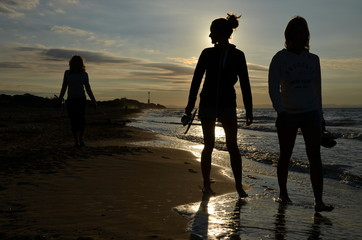 silhouettes of three women going on the beach
