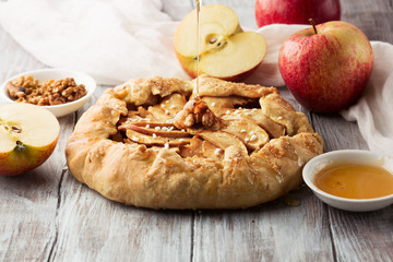 Homemade crostata with ripe apples, nuts and maple syrup on rustic white wooden background, selective focus