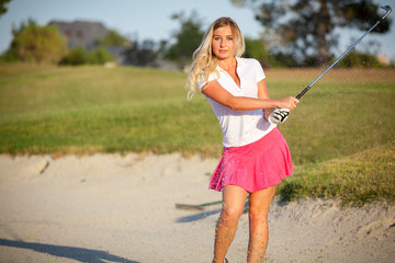 Beautiful young girl playing golf in sand trap on course.