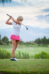 Blonde female golfer swinging club on golf course green with cop