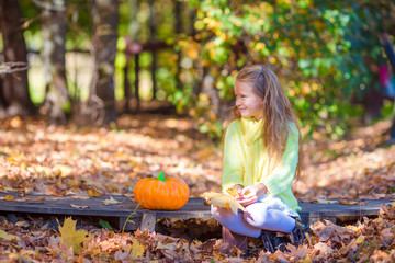 Wall Mural - Adorable little girl with a pumpkin for Halloween outdoors at beautiful autumn day