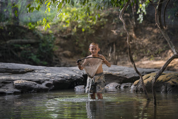Little asian boy fishing in the river.