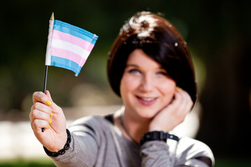Transgender girl holding out with her arm trans pride flag. Flag in focus and trans girl out of focus.