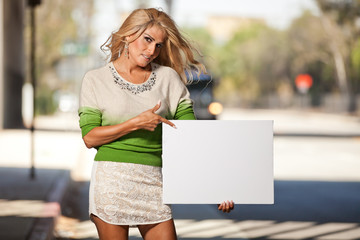 Latina Transgender female pointing at blank poster board sign