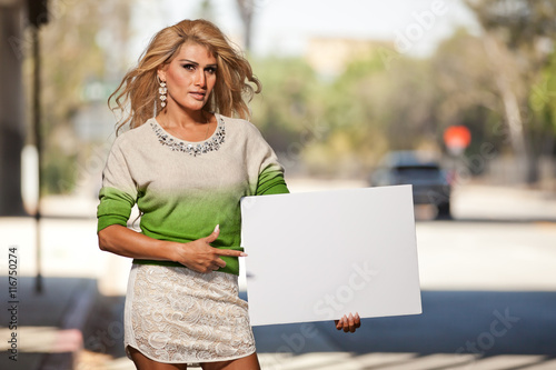 latina transgender female pointing at blank poster board sign stock