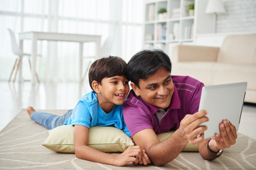 Indian father and son lying on floor and watching cartoons on digital tablet