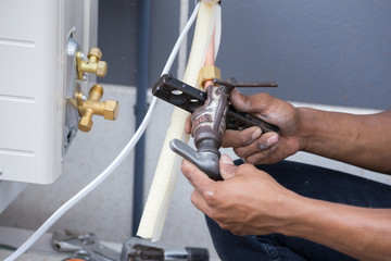 installation of air conditioner, worker connects copper pipe