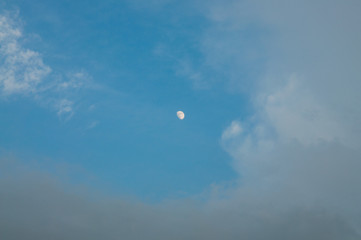 The moon and clouds on blue sky background.