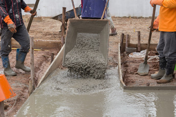 worker pouring cement from cart to floor