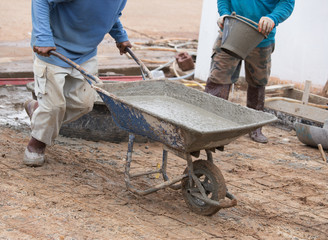 worker pushing barrow with wet cement to pouring concrete floor