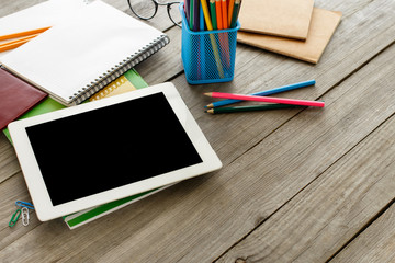 White tablet with blank screen and office supplies