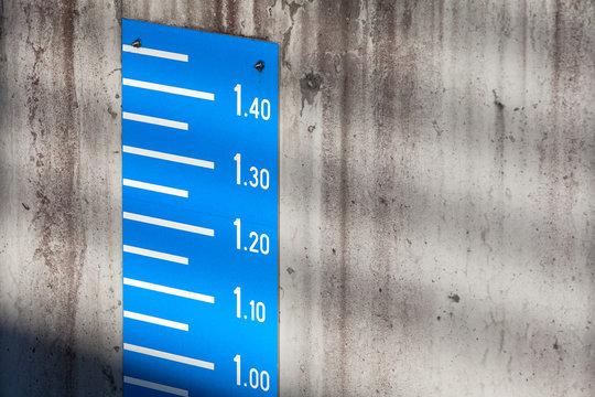 Blue tide level measurement scale on concrete wall