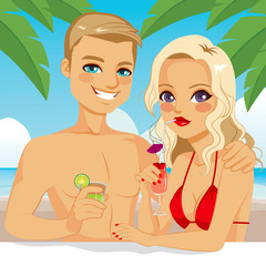Attractive blonde couple drinking cocktail and juice relaxing at the beach on vacation