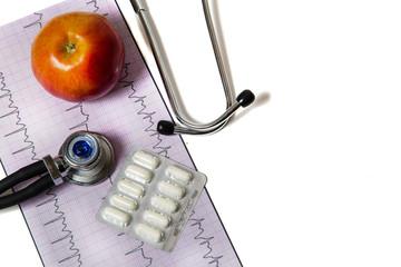 Стетоскоп с яблоком и таблетками на кардиограмме
