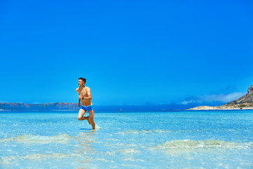 strong athletic man with bared torso running on the beach along the sea front