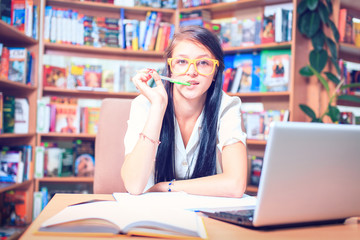 girl student with glasses reading books in the library