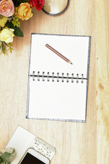 Pencil and open notebook on wood background in selective focus.