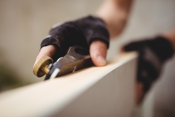 Carpenter's hand leveling a wooden frame with block plane
