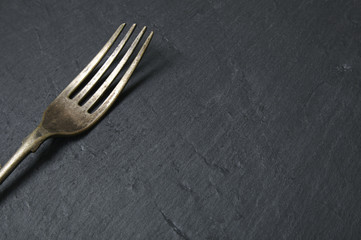 Antique silver fork on a rustic slate background