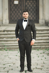 Stylish groom posing on background old castle