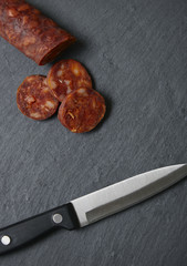 Sliced Spanish chorizo sausage on a rustic slate chopping board background