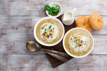 Mushroom cream soup with champignons and fresh basil on a wooden table, top view