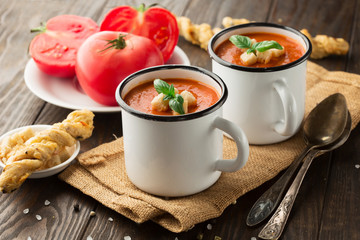 Homemade Tomato red pepper soup on rustic wooden table, selective focus