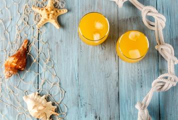 Orange juice in glass and seashells