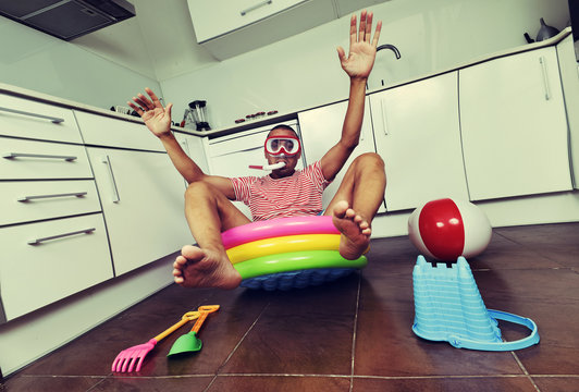 man swimming in an inflatable water pool, indoors
