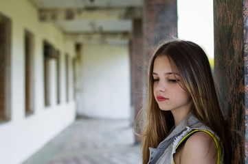 Teenage girl standing near wall in abandoned building and thinking about something