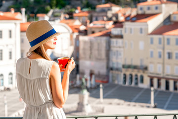 Young female traveler using mobile phone sitting on the central square in Piran old town. Traveling in Slovenia