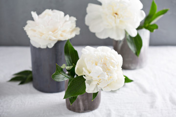 White peonies in gray handmade cups