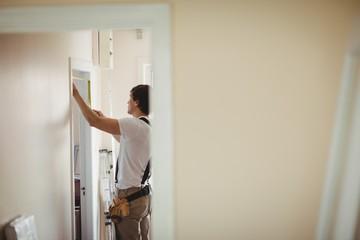 Carpenter measuring a door frame