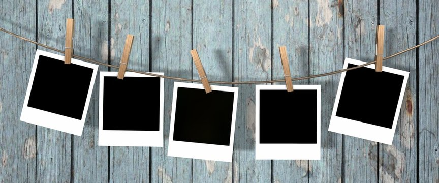 five blank instant photos hanging on the clothesline