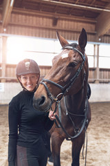 Horse nuzzling a smiling attractive young woman