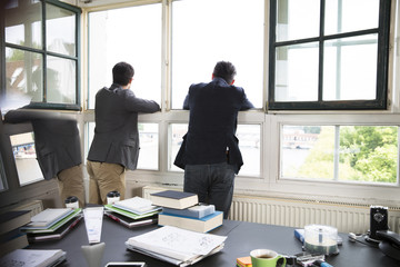 Two businessmen looking out of window