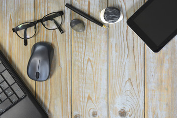 Wooden desk table with laptop computer, tablet, fountain pen, mouse, glasses and zen stones decoration with empty copy space