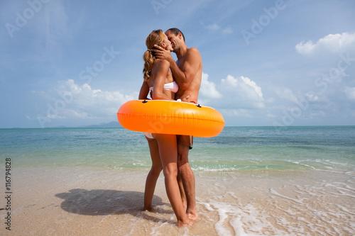 """Couple Qui S Embrasse couple qui s'embrasse sur la plage dans une bouée orange"""" stock"""