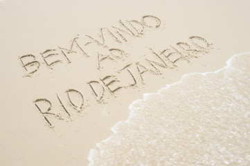 Wave approaches Brazil Bem-vindo ao Rio de Janeiro (Welcome to Rio) message in Portuguese handwriting in sand
