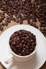 Coffee beans and coffee in cup on burlap. Selective focus
