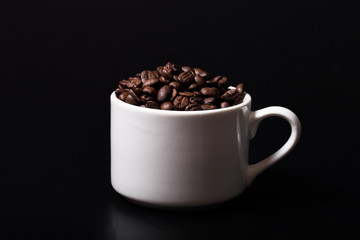 Coffee beans in the cup on black background