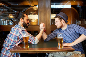 men drinking beer and arm wrestling at bar or pub