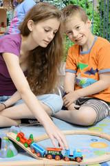 Teenager als Babysitter spielt Holzeisenbahn mit Kind in Kinderzimmer