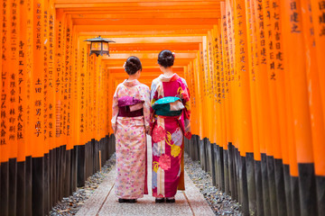 Spoed Fotobehang Kyoto Two geishas among red wooden Tori Gate at Fushimi Inari Shrine in Kyoto, Japan. Selective focus on women wearing traditional japanese kimono.